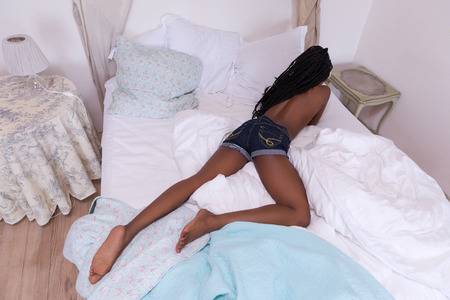 Beautiful African woman with long braids relaxing on her bed in the morning