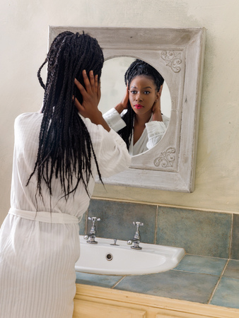 Pretty young african american woman doing her morning routine in front of the bathroom mirror Stok Fotoğraf - 122346955