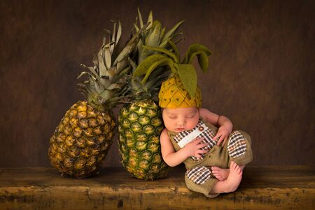Cute composite image with fresh pineapples and a newborn baby in felted pineapple hat Stock Photo