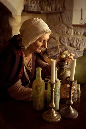 Woman in medieval outfit working as an alchemist or witch in the kitchen of a French medieval castle - with property release 스톡 콘텐츠