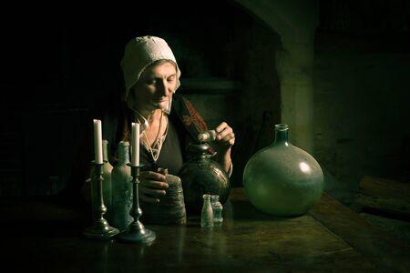 Frau in mittelalterlichem Outfit, die als Alchemist oder Hexe in der Küche einer französischen mittelalterlichen Burg arbeitet - mit Eigentumsfreigabe