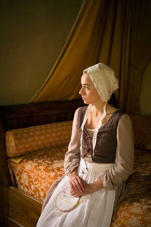 Retrato de estilo Vermeer de una joven sirvienta en traje renacentista sentada en una cama antigua con su trabajo de bordado Foto de archivo