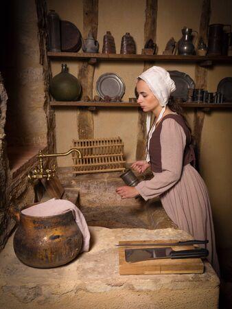 Mujer joven en constume campesino medieval trabajando en una auténtica cocina antigua en una propiedad liberada chateau francés
