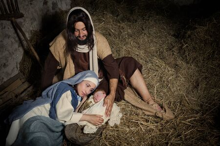 Live-Weihnachtskrippe in einer alten Scheune - Reenactment-Spiel mit authentischen Kostümen. Das Baby ist eine (im Eigentum freigegebene) Puppe.