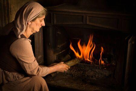 Renaissance-Altmeisterporträt einer Bäuerin, die einem brennenden Feuer Holz hinzufügt Standard-Bild