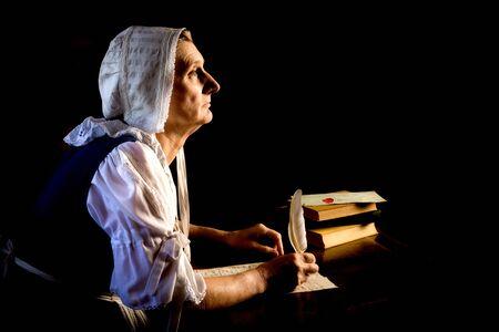 Rembrandt-Stil oder Renaissance-Porträt einer Frau, die einen Brief mit Federkiel schreibt