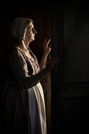 Mujer esperando en la puerta en la oscuridad Foto de archivo