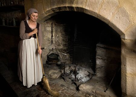 Woman dressed in renaissance maid costume using her broom to clean the fireplace in the kitchen of a property released authentic medieval castle in France Standard-Bild