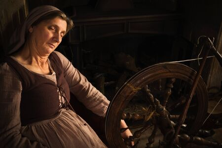 Renaissance Old Master portrait of a woman with antique spinning wheel in front of a fireplace Standard-Bild