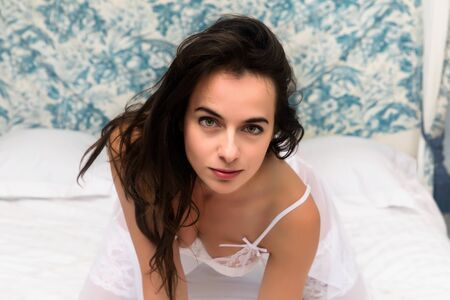 Beautiful young brunette wearing a sheer white nightgown posing on an antique canopy bed in a victorian bedroom