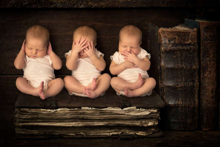 Three sleeping newborn babies doing the hear see speak no evil gestures while sitting on a stack of antique books Stockfoto