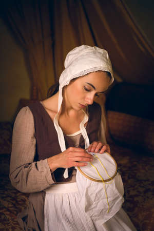 Vermeer style portrait of a young maid in renaissance costume sitting on an antique bed with her embroidery work Foto de archivo