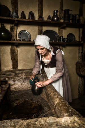Woman dressed as a medieval peasant maid working in an authentic kitchen in a French castle