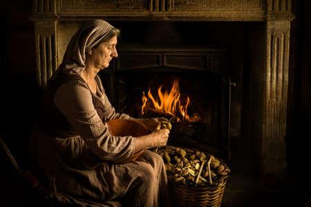 Renaissance old master portrait of a peasant woman peeling potatoes at her fireplace Standard-Bild