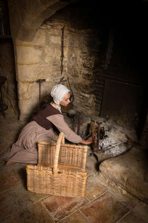 Renaissance portrait in Rembrandt style of a young woman in medieval peasant costume working near the authentic fireplace of a property released French castle Stock fotó