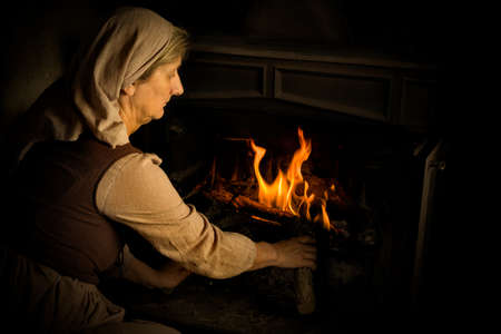 Renaissance old master portrait of a peasant woman adding wood to a burning fire