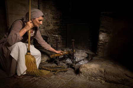 Woman in renaissance maid outfit adding wood logs to the burning fire in the kitchen of a property released authentic medieval castle in France