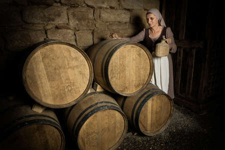 Woman in medieval peasant outfit checking wine barrels in the cellar of a property released authentic medieval castle in France Stock fotó