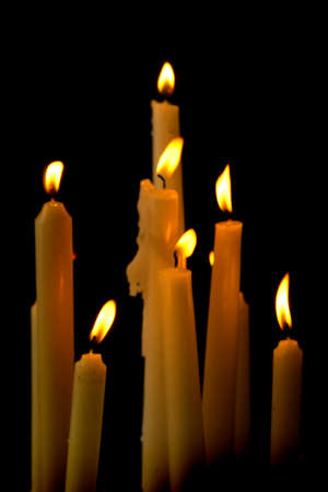 Row of white burning church candles against a black background Archivio Fotografico