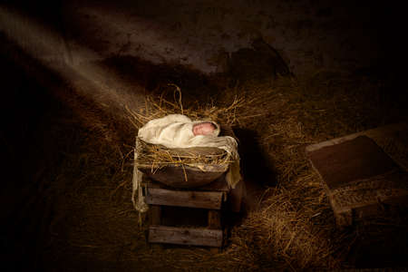 Dark stable with a doll playing jesus as a baby in the manger