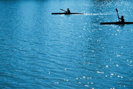 paddles: A black silhouettes of  child sportsmen on paddles (kayaks) Stock Photo