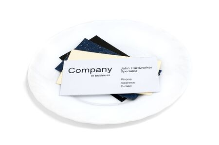 hardworker: Business cards on white plate isolated on white background