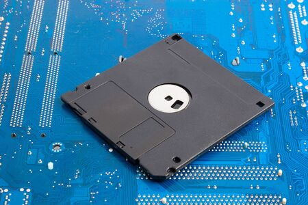 the outdated: Outdated technology memories: black floppy disk on blue background Stock Photo