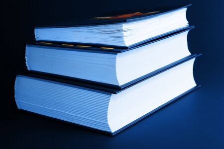 textbooks: Knowledge is the light: three books isolated on black with blue lighting