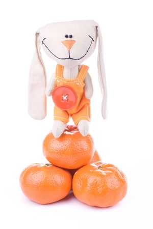 romper: Smiling fabric hare toy in romper suit owns oranges Stock Photo