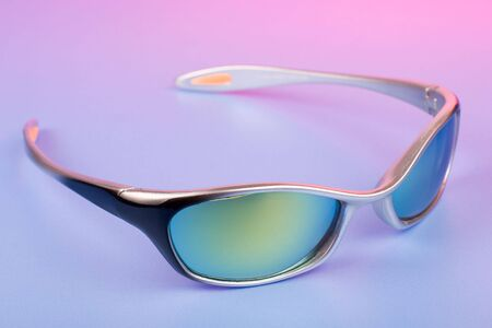 Fashionable sunglasses on color background under pink light photo