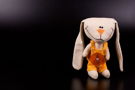 romper: Funny hare toy on black background with copyspace