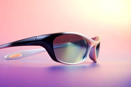 Summer - fashionable sunglasses on color background under sun light  photo