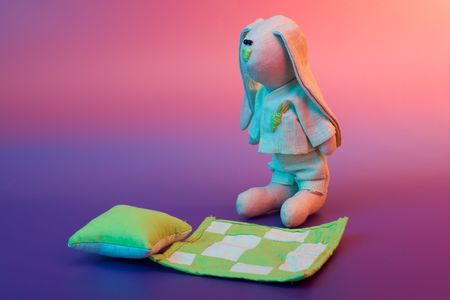 Go to sleep - sleepy hare toy on color background  photo