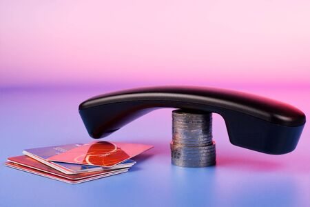 Business glamour - phone handset; credit cards and coins stack on soft pastel color gradient  photo
