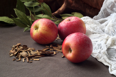 cinnamon bark: There are apples and cinnamon bark with a laurel branch as background.