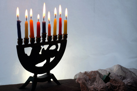 There are Hanukkah Menorah with lighted candles and a sevivon  on the windowsill. photo