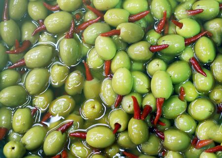 olives with hot red paper, chilli, picking from plants during harvesting, green