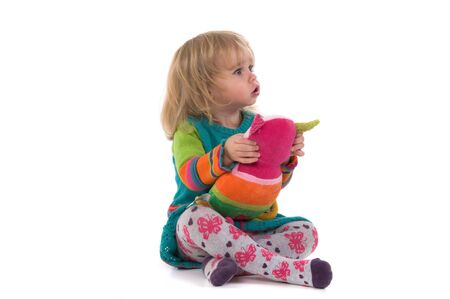 Baby with toy sitting on the floor and watching on the corner