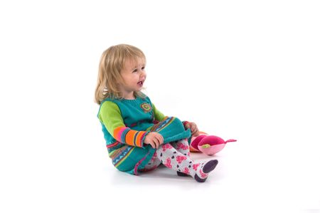 Happy baby with toy sitting on the floor