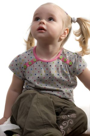 ponytails: Closeup portrait of little girl with ponytails sitting on the floor Stock Photo