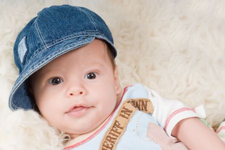 Shot of trendy newborn boy in denim cap