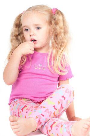 Petite fille mignonne en studio, manger des bonbons