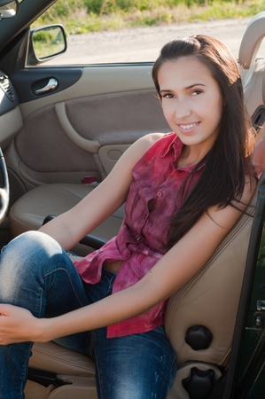 Beautiful brunette woman sitting in cabrio photo