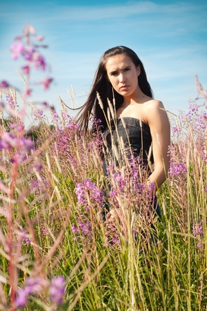 Woman standing in grass and flowers photo