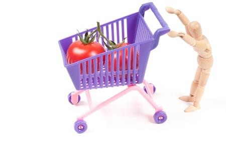 shoppingcart: Conceptual photo with wooden man and shopping-cart Stock Photo