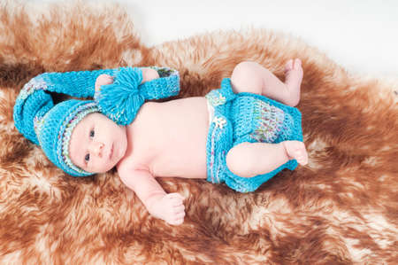 Shot of newborn baby in knitted blue clothes lying on fur photo