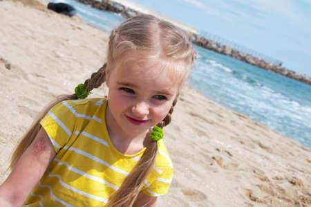 Kleines Mädchen sitzt am Strand Standard-Bild