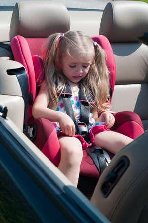 Kleines nettes Mädchen sitzt im Autositz Standard-Bild
