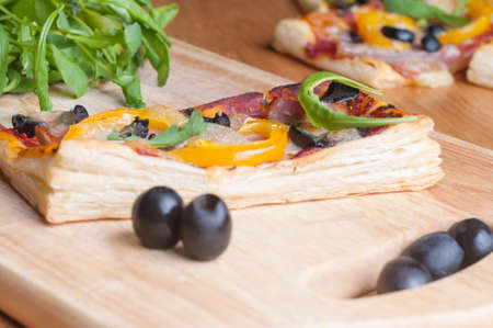 ruccola: puff pastry cake with ruccola and olives Stock Photo