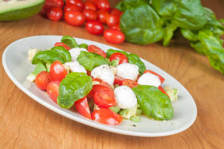 Salad with avocado, tomatoes and basil on the wooden table Stock Photo - 22224604